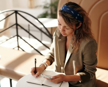 woman in brown blazer writing on notebook