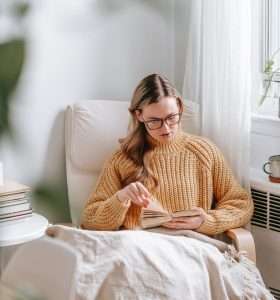 young woman reading book in cozy armchair
